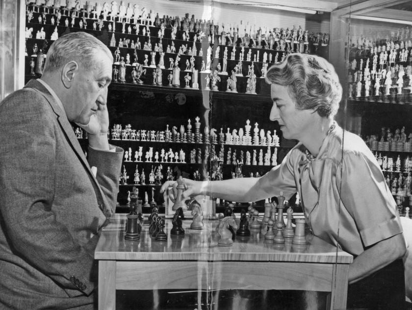 Gregor Piatigorsky, left, and his wife, Jacqueline, playing chess in front of their chess collection in 1962.