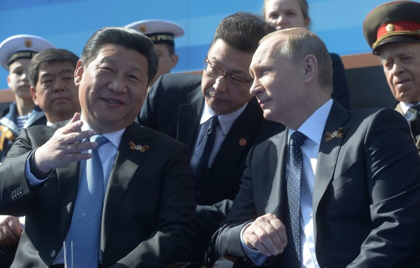 In this image provided through the news agency RIA Novosti, Russian President Vladimir Putin, right, and Chinese President Xi Jinping attend the military parade to mark the 70th anniversary of Victory Day on May 9 in Moscow.