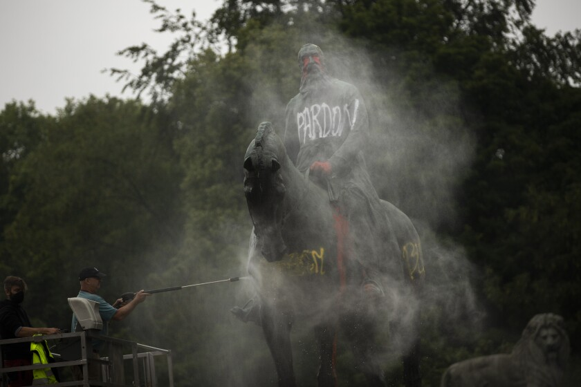 Workers clean graffiti from a statue of Belgium's King Leopold II in Brussels on Thursday, June 11, 2020, that was targeted by protesters during a Black Lives Matter demonstration. The protests sweeping the world after George Floyd's death in the U.S. have added fuel to a movement to confront Europe's role in the slave trade and its colonial past. Leopold is increasingly seen as a stain on the nation where he reigned from 1865 to 1909. Demonstrators want him removed from public view. (AP Photo/Francisco Seco)