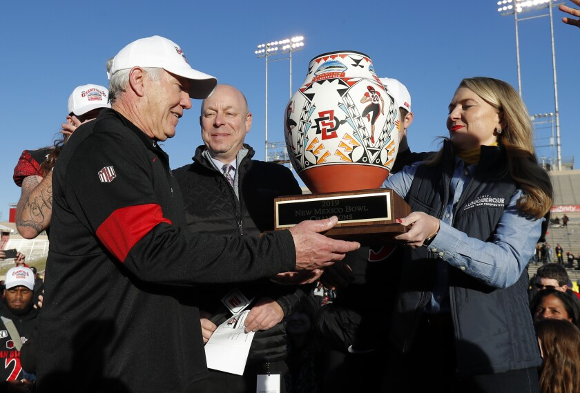 San Diego State head coach Rocky Long receives the trophy after SDSU beat Central Michigan 48-11 in the New Mexico Bowl.