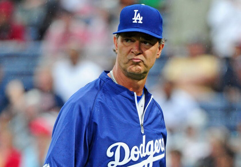 Dodgers Manager Don Mattingly heads back to the dugout after making a pitching change against the Atlanta Braves.