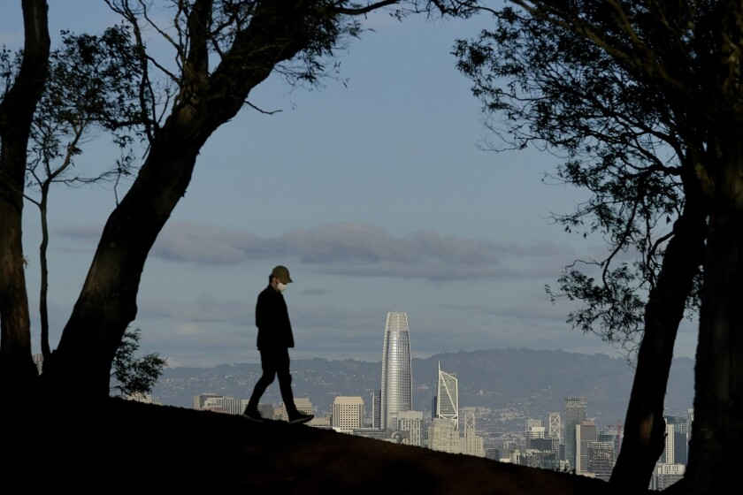 A person wearing a face mask walks atop Tank Hill in front of the skyline during the coronavirus pandemic in San Francisco.