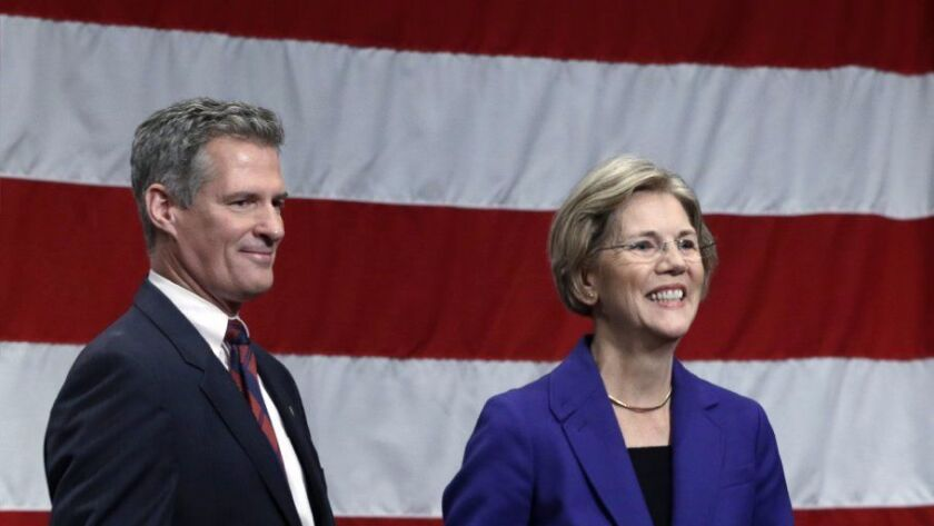 Former Massachusetts Senator Scott Brown, a Republican, leaves the stage with Sen. Elizabeth Warren, the Democrat who defeated him, after a 2012 debate in Springfield, Mass.