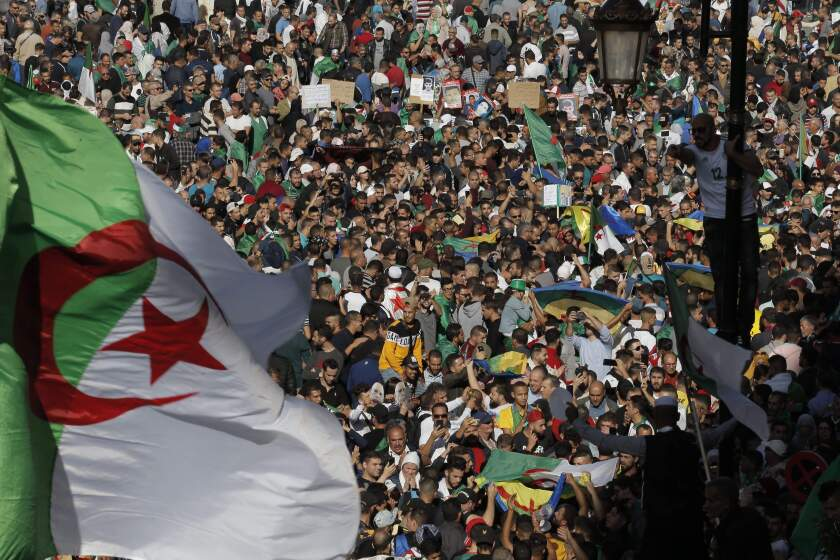 Algerian demonstrators take to the streets in the capital Algiers to protest against the government, in Algeria, Friday, Nov. 1, 2019. Police struggled Friday to contain thousands of Algerian demonstrators surging through the streets of the capital to protest next month's presidential election and celebrate 65 years since Algeria's war for independence from France. (AP Photo/Toufik Doudou)