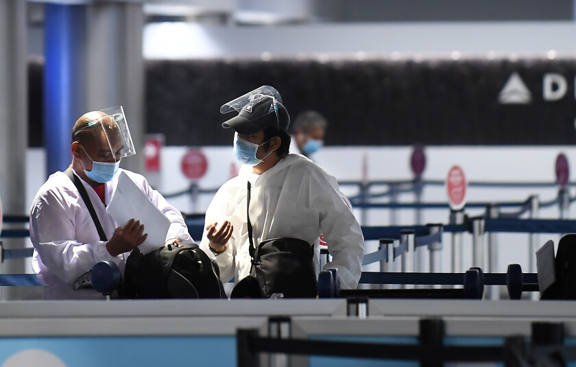 Travelers in face shields, masks and protective clothing talk at a virtually empty LAX.
