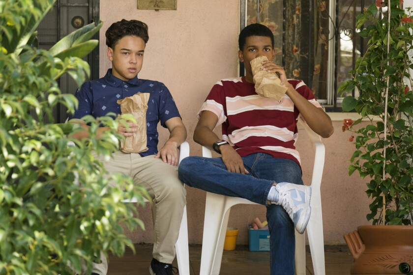 Two teen boys drink out of paper bags on a porch.