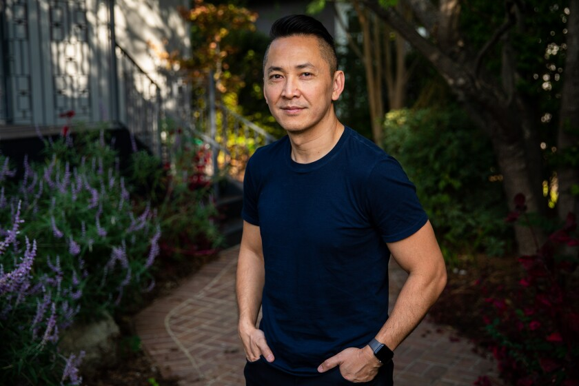 Viet Thanh Nguyen stands on a brick path surrounded by plants.