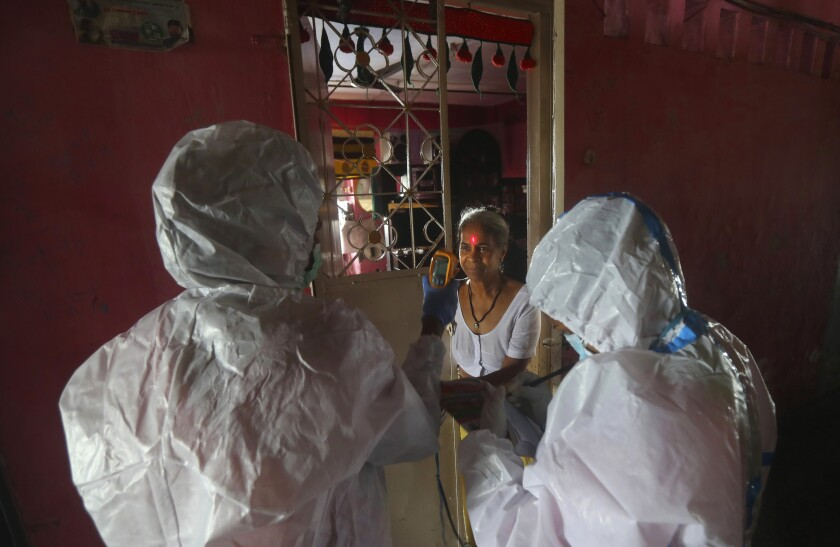 Health workers screen people for COVID-19 symptoms at a residential building in Dharavi , one of Asia's biggest slums, in Mumbai, India, Friday, Aug. 7, 2020. As India hit another grim milestone in the coronavirus pandemic on Friday, crossing 2 million cases and more than 41,000 deaths, community health volunteers went on strike complaining they were ill-equipped to respond to the wave of infection in rural areas. (AP Photo/Rafiq Maqbool)