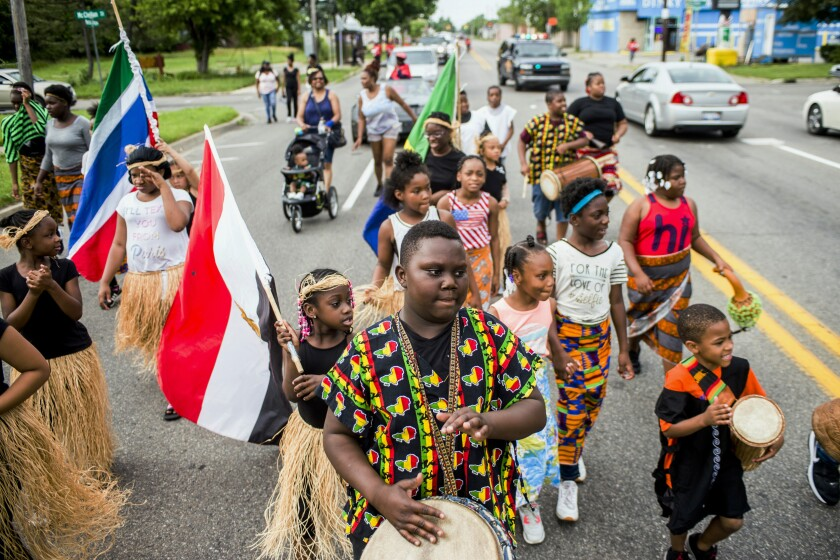 FILE - In this June 19, 2018, file photo, Zebiyan Fields, 11, at center, drums alongside more than 20 kids at the front of the Juneteenth parade in Flint, Mich. Juneteenth, the holiday that commemorates the end of slavery in the United States, originated 155 years ago. (Jake May/The Flint Journal via AP, File)
