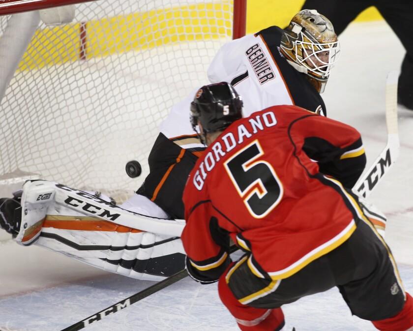Flames' Mark Giordano, left, scores a short-handed goal against Ducks goalie Jonathan Bernier during the third period on Dec. 4.