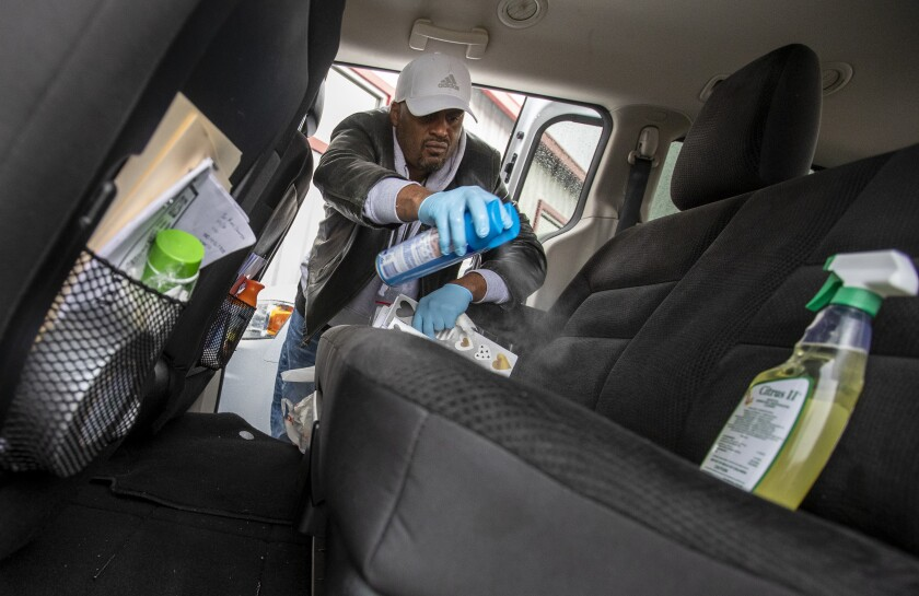 LOS ANGELES, CALIF. -- FRIDAY, MARCH 13, 2020: HOPICS outreach nurse Kenya Smith sprays sanitizer inside a van before going out to look for homeless people as part of the outreach program in Los Angeles, Calif., on March 13, 2020. (Brian van der Brug / Los Angeles Times)