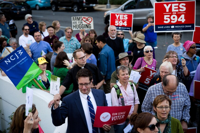 Supporters of Initiative 594 gather in Seattle in October. The initiative, approved Tuesday, imposes background checks on gun sales in Washington.