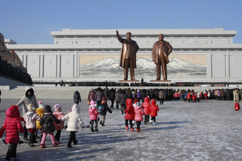 FILE - In thus Dec. 16, 2014 file photo, North Koreans gather at the Mansu Hill where the statues of the late leaders Kim Il Sung, and Kim Jong Il tower over them, in Pyongyang, North Korea.  Cybersecurity researchers say it's possible that North Korea is behind a recent hacking that resulted in th