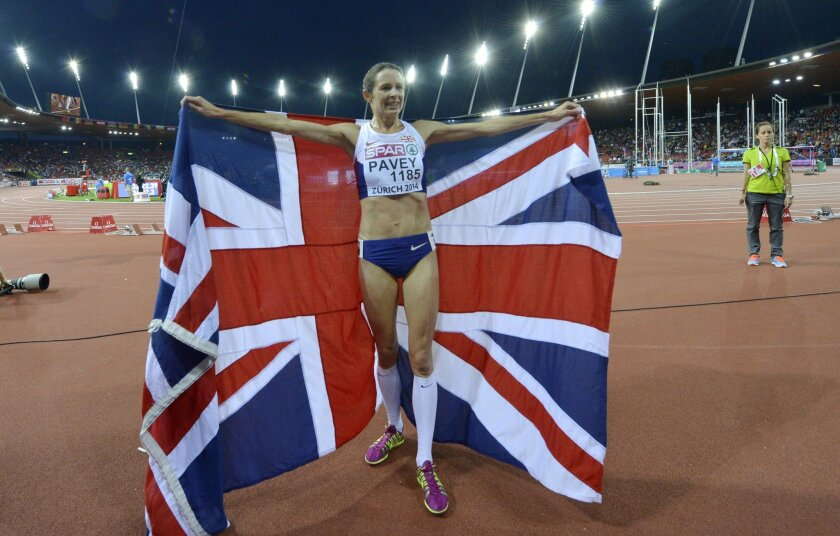 Britain's Jo Pavey celebrates with her country's flag after winning the gold medal in the women's 10,000m final during the European Athletics Championships in Zurich, Switzerland, Tuesday, Aug. 12, 2014. (AP Photo/Martin Meissner)