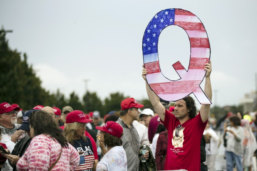 FILE - In this Aug. 2, 2018, file photo, a protester holds a Q sign as he waits in line with others to enter a campaign rally with President Donald Trump in Wilkes-Barre, Pa. Casino giant Caesars Entertainment Inc. said Wednesday, Sept. 1, 2021, that a conference scheduled next month in Las Vegas by a group espousing the fringe conspiracy theory known as QAnon won't be held at any Caesars property. (AP Photo/Matt Rourke, File)