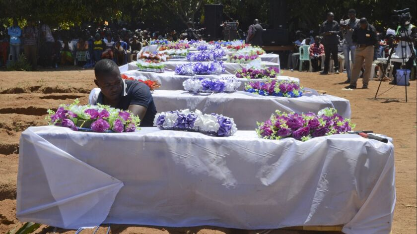 Coffins for some of the victims of the capsized passenger ferry Nyerere are set out during a mass burial ceremony on Ukara Island, Tanzania, on Sunday, Sept. 23, 2018.