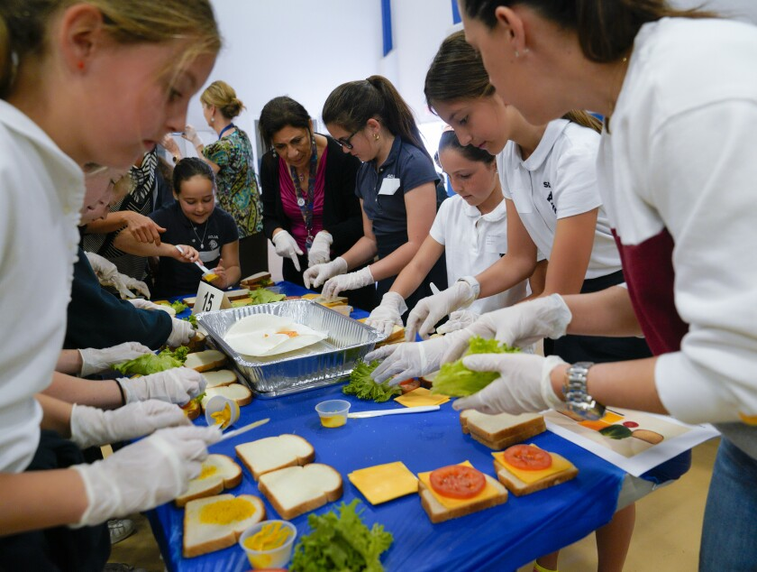 Students from San Diego Jewish Academy on Monday race to assemble sandwiches to beat the previous Guinness World Record of 490, for most sandwiches assembled in three minutes. In the end, the students had assembled 868 sandwiches which consisted of two slices of bread, mustard, tomato, two slices of cheese and lettuce.
