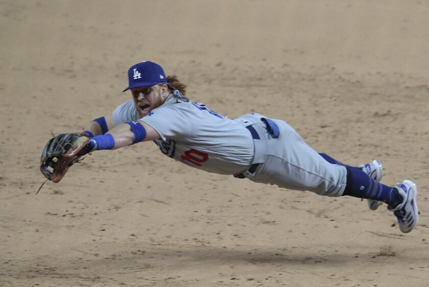 Dodgers third baseman Justin Turner dives but can't stop a brace by the Atlanta Braves Dansby Swanson.
