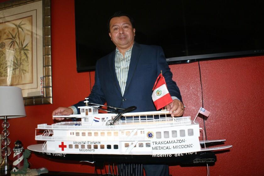 Luis Heredia muestra el barco-hospital en miniatura con el que desea llegar a la región amazónica de Perú