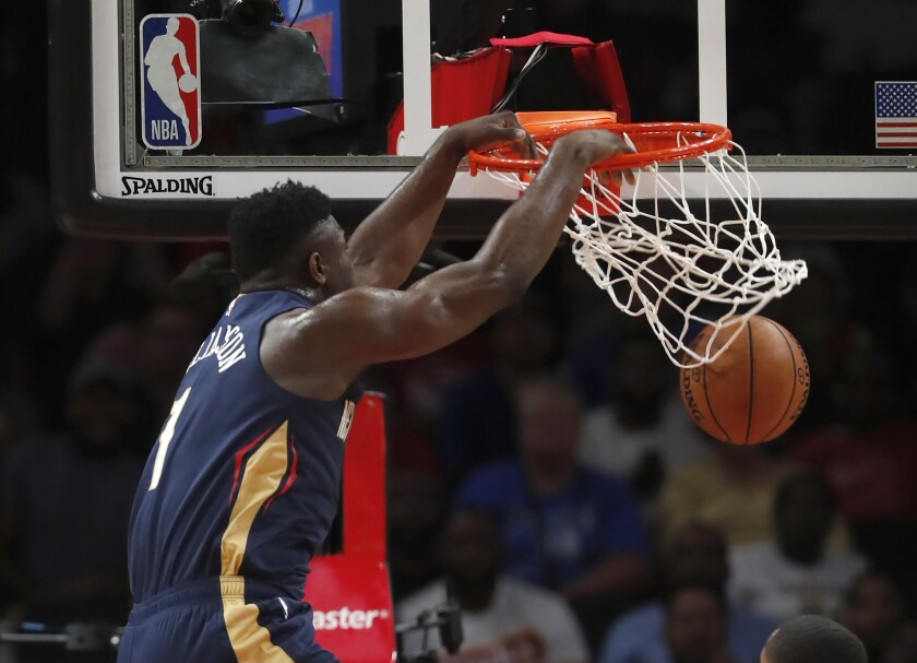 New Orleans Pelicans forward Zion Williamson scores during a preseason game.