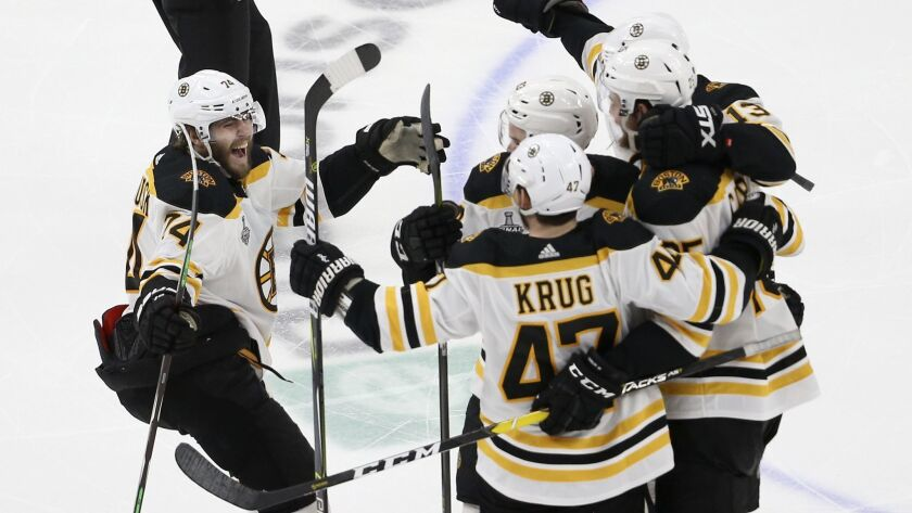 Boston Bruins left wing Jake DeBrusk (74) joins the celebration after Brandon Carlo, right, scored a