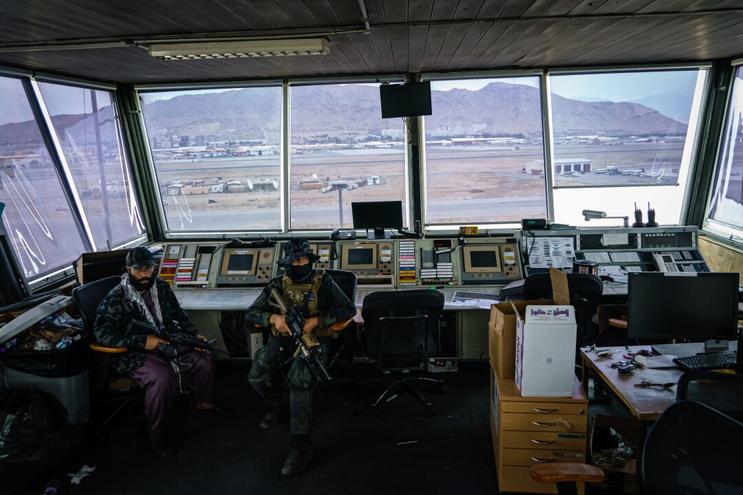 Taliban fighters sit at controller's stations in the Kabul airport's  control tower