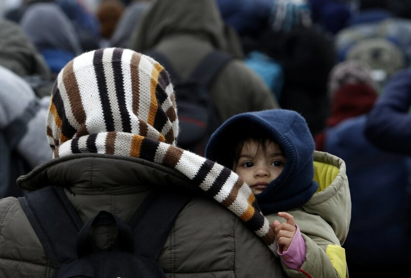 A baby looks back over woman's shoulder as they move with a group of refugees towards the border with Serbia, from the transit center for refugees near northern Macedonian village of Tabanovce, Wednesday, Feb. 10, 2016. Macedonian authorities are reinforcing a barrier at the country's border with G