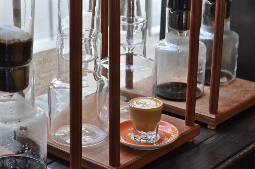 A cortado sits near the row of siphon coffeemakers brewing cold drip coffee at the Cafe Demitasse in Little Tokyo.