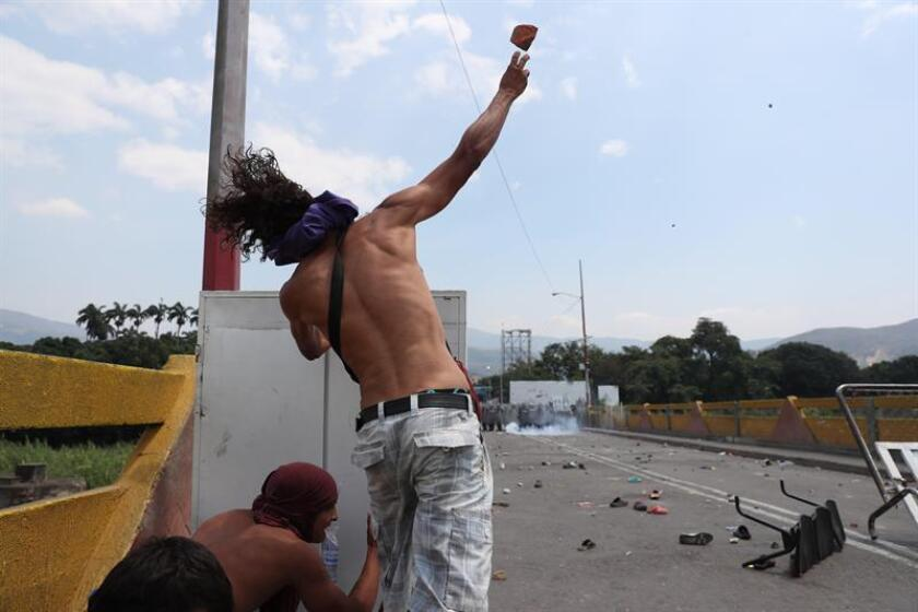 A protester throws a rock at Venezuelan police during a standoff on the Simon Bolivar International Bridge in Cucuta, Colombia, on Feb. 23, 2019. Hundreds of civilians gathered on the Simon Bolivar International Bridge in Cucuta, Colombia, on Feb. 23, 2019, in a bid to force the delivery of humanitarian aid shipments to crisis-racked Venezuela. EPA-EFE/Ernesto Guzman Jr.