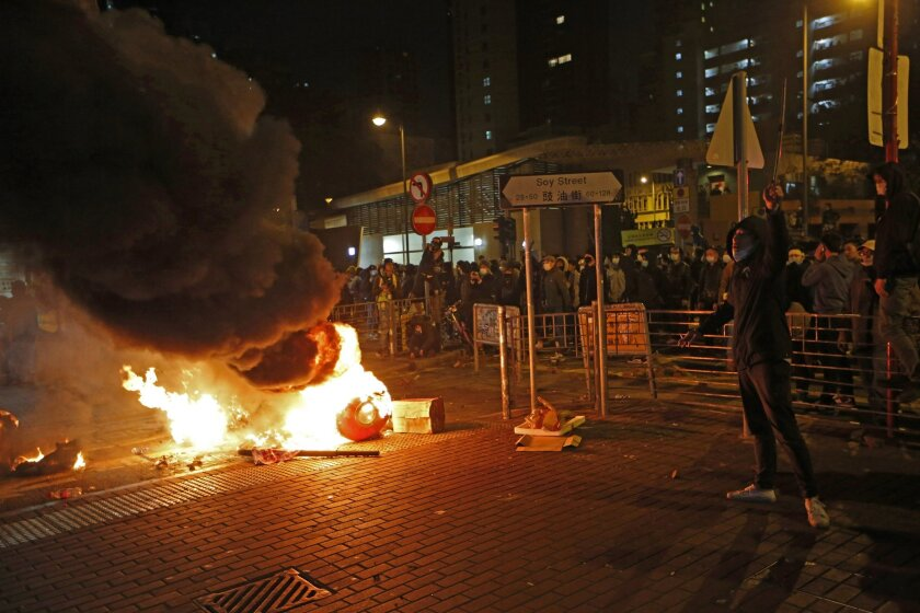 Smoke rises as protestors set fires on a street in the Mong Kok district of Hong Kong, Tuesday, Feb. 9, 2016. Hong Kong's Lunar New Year celebration descended into chaotic scenes as protesters and police clashed over a street market selling fish balls and other local holiday delicacies. (AP Photo/K