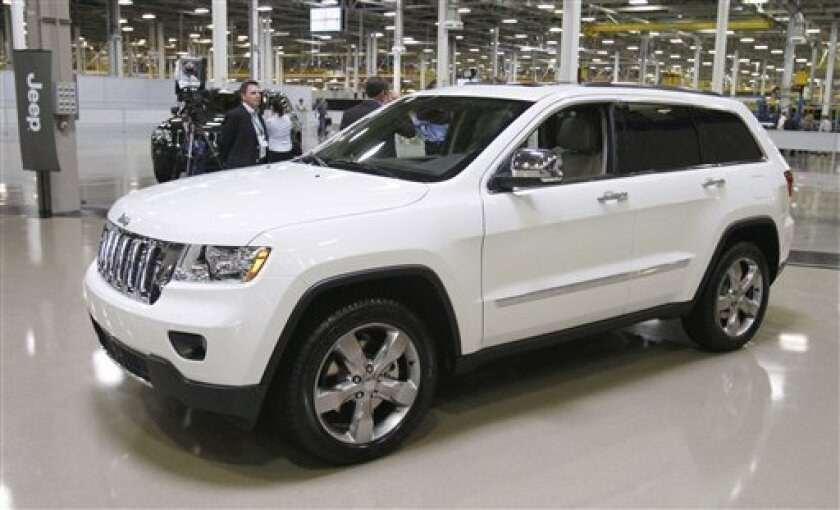 FILE - This May 21, 2010 file photo shows a 2011 Jeep Grand Cherokee at the Jefferson North Assembly in Detroit. Chrysler said Monday, Nov. 8, 2010, it narrowed its losses by 51 percent to $84 million in the third quarter, buoyed by strong sales of the new Jeep Grand Cherokee. (AP Photo/Carlos Osorio, File)