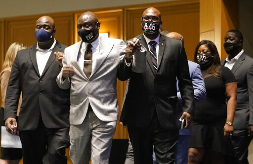 Floyd family attorney Ben Crump, center, walks in with George Floyd's brothers Philonise Floyd, right, and Rodney Floyd, left, before they announced a $27 million civil lawsuit settlement between the Floyd family and the City of Minneapolis Friday, March 12, 2021, in Minneapolis. (David Joles/Star Tribune via AP)