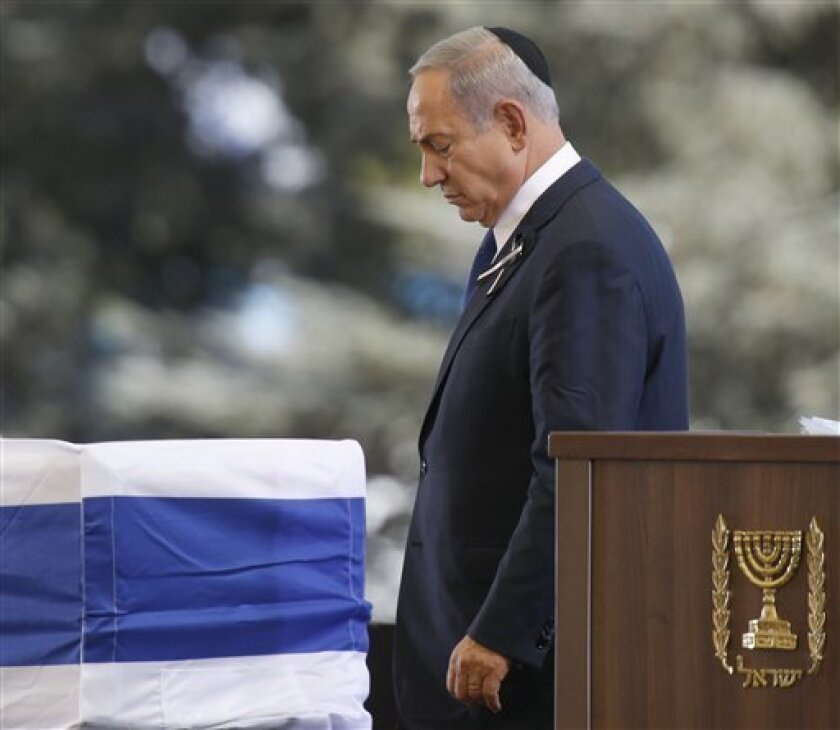El primer ministro israelí, Benjamin Netanyahu, psada junto al ataúd que contiene los restos mortales del expresidente Shimon Peres, envuelto en la bandera de Israel, tras intervenir en su funeral en el cementerio nacional del Monte Herzel, en Jerusalén, el 30 de septiembre de 2016.