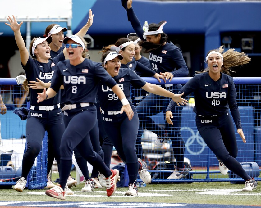 U.S. softball players celebrate after Kelsey Stewart's walk-off homer to right field to cap a 2-1 win over Japan.