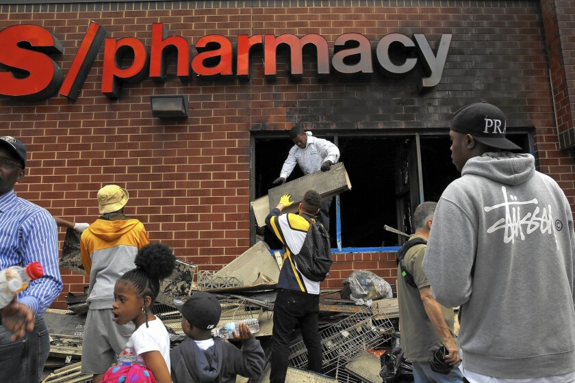 Volunteers clean up a CVS drugstore in Baltimore that was looted and burned Monday night.