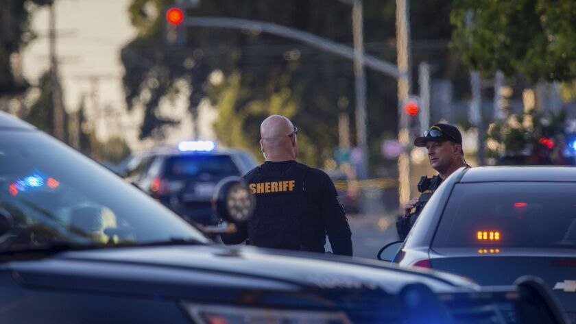 Sacramento County Sheriff's Department deputies talk, Wednesday, June 19, 2019, on Grove Avenue in S