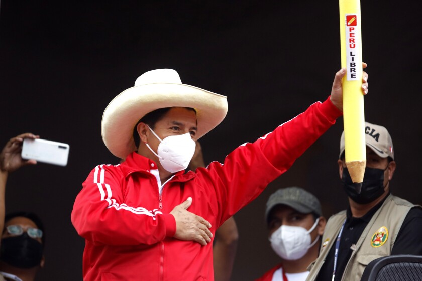 Pedro Castillo holds up a large, mock pencil during his closing campaign rally in Lima, Peru.