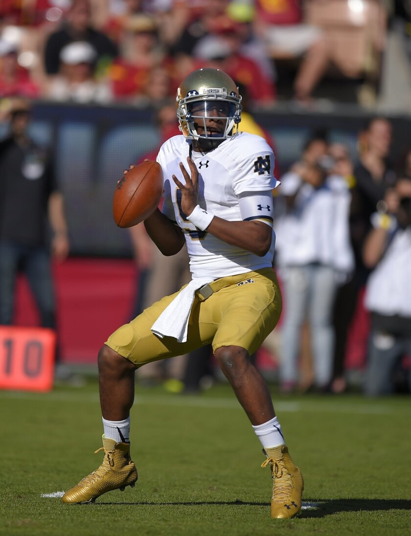 FILE - In this Nov. 29, 2014 file photo, Notre Dame quarterback Everett Golson gets set to pass during the first half an NCAA college football game against Southern California in Los Angeles. With a week until the opener against Texas State, Florida State head coach Jimbo Fisher still is trying to decide between Everett Golson or Sean Maguire as the starting quarterback. (AP Photo/Mark J. Terrill, File)