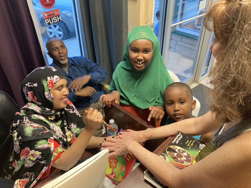 Mushtak Bireh and her brother, Musab, watch their mother Foos give a henna manicure in Postville, Iowa.