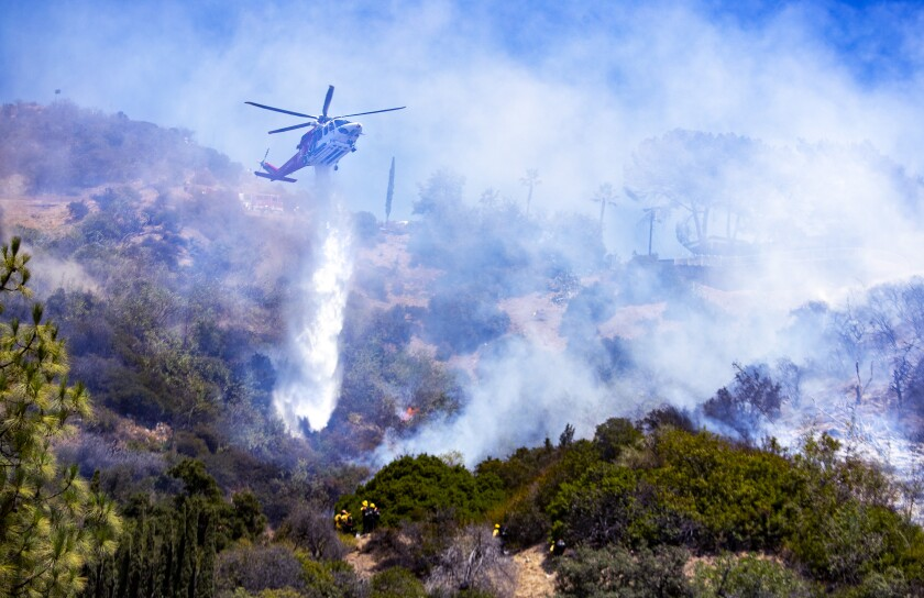 A helicopter drops water on a brushfire.