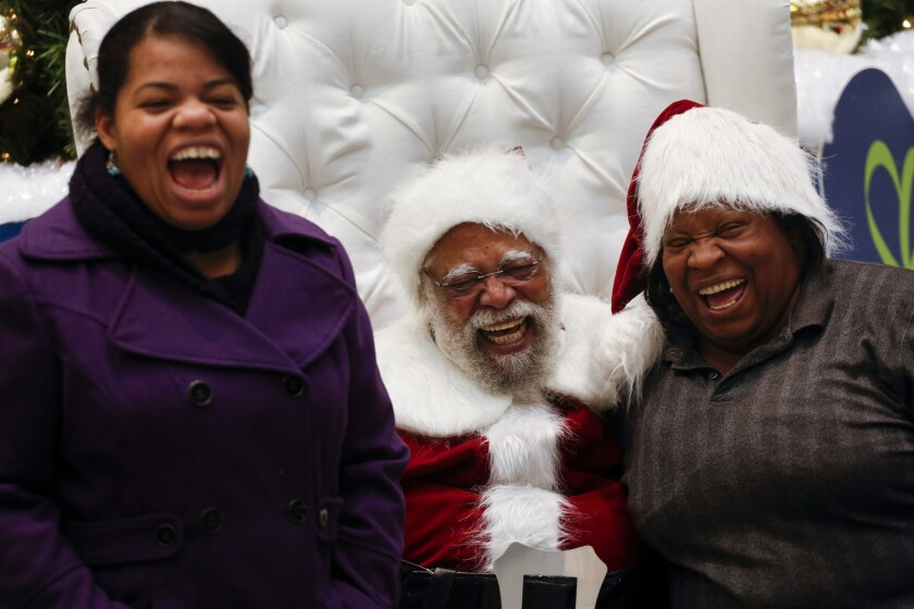 Kelly Ross, left, and her mom, Tracy Price, share a big laugh with Santa at the Baldwin Hills Crensh