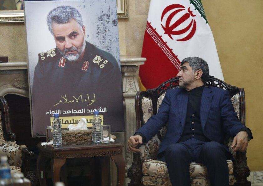 """Iran's Ambassador to Lebanon Mohammed Jalal Feiruznia, looks to a portrait of the Iranian Revolutionary Guard Gen. Qassem Soleimani, as he receives condolences at the Iranian embassy, in Beirut, Lebanon, Friday, Jan. 3, 2020. President Donald Trump says the Iranian military commander who was killed by a U.S. airstrike in Iraq was """"plotting to kill"""" many Americans."""