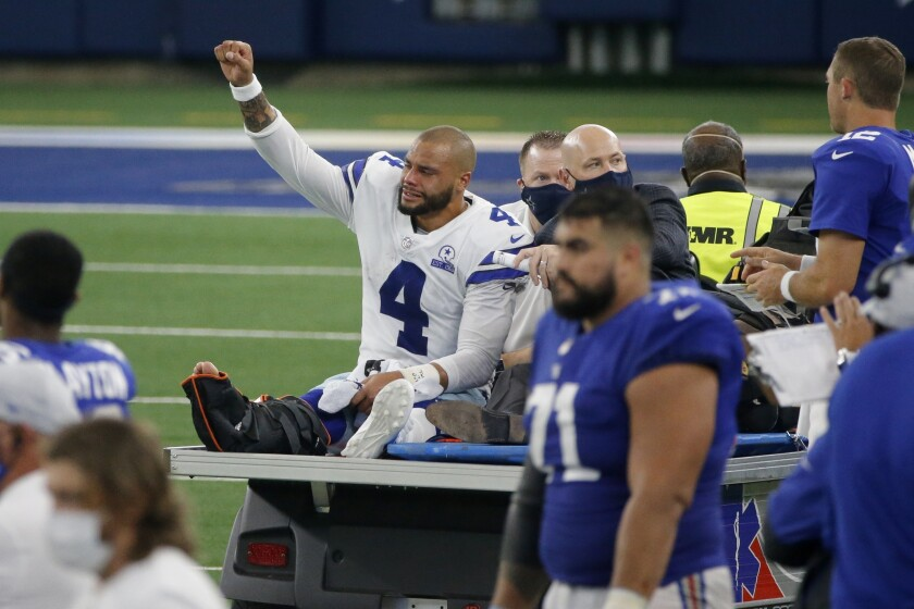FILE - In this Oct. 11, 2020, file phot, Dallas Cowboys quarterback Dak Prescott (4) lifts his fist to cheers from fans as he is carted off the field after suffering an injury while running the ball during the second half of the team's NFL football game against the New York Giants in Arlington, Texas. The Cowboys are on the verge of a lost year, when they had hoped to contend, after a broken ankle ended the quarterback's season. (AP Photo/Michael Ainsworth, File)