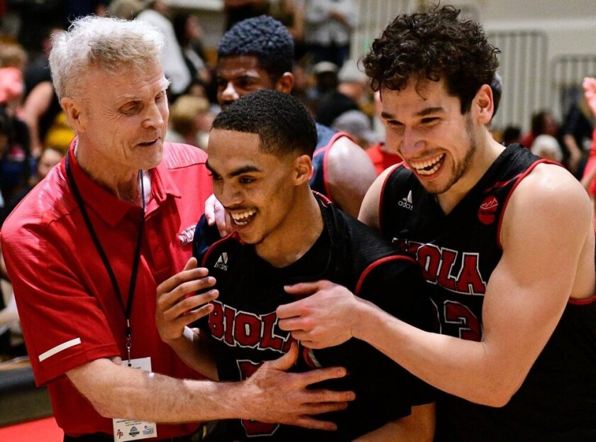 Biola University coach Dave Holmquist celebrates with players during a recent game.