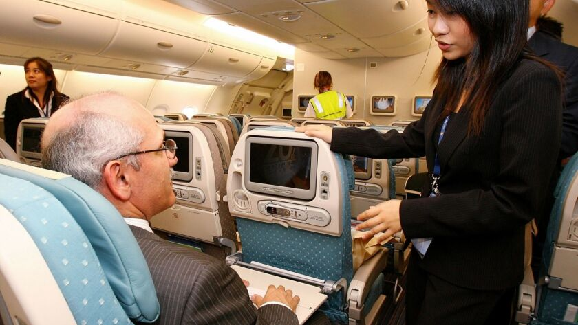 A Singapore Airlines staff member explains the features aboard the new Singapore Airlines Airbus A380. The airline was ranked the best by Skytrax, according to the latest survey of more than 20 million travelers around the world by the Skytrax World Airport Awards.