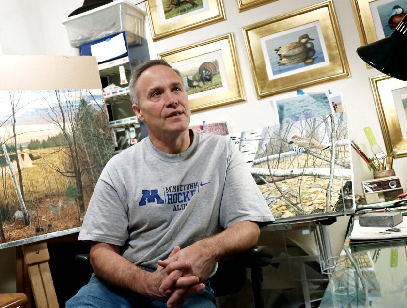In this Dec. 1, 2014 photo, outdoor artist Stephen Hamrick talks about his paintings in his home studio in Lakeville, Minn. Hamrick recently won the Minnesota DNR's 2015 walleye stamp contest for his rendition of the toothy fish. (AP Photo/Jim Mone)