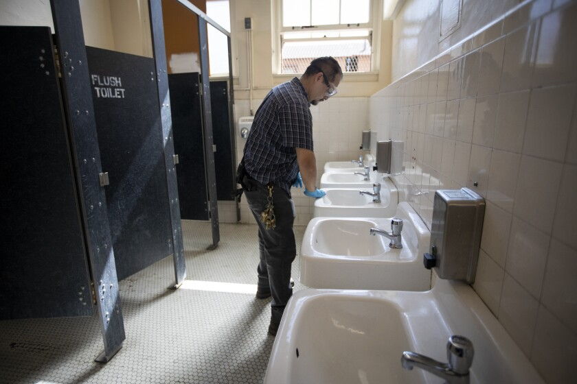 Martin Nevarez cleans a bathroom at Burroughs Middle School in Los Angeles on Tuesday.