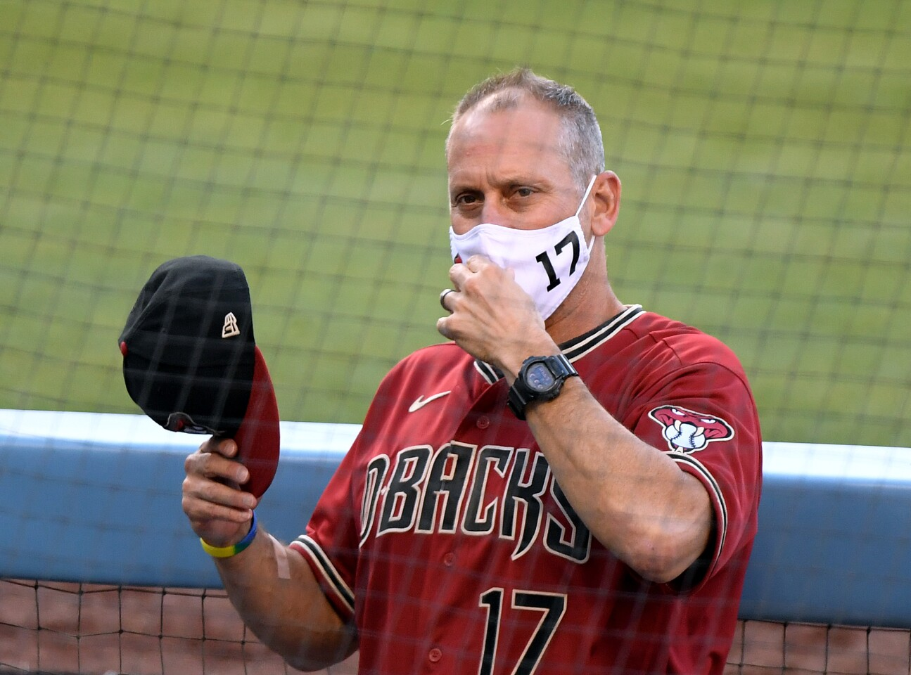 LOS ANGELES, CALIFORNIA - JULY 20: Manager Torey Lovullo #17 of the Arizona Diamondbacks adjust his mask in the dugout before a preseason game the Los Angeles Dodgers during the coronavirus (COVID-19) pandemic at Dodger Stadium on July 20, 2020 in Los Angeles, California. (Photo by Harry How/Getty Images)