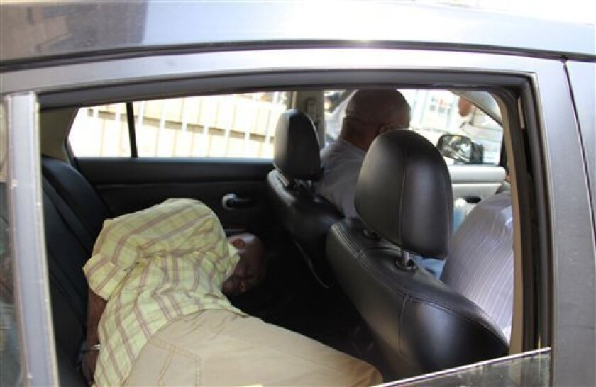Henry Okah, a Nigerian ex-militant leader seeks cover on the back seat of a vehicle as he leaves the court in Johannesburg Monday Oct. 4. 2010. At a court hearing in Johannesburg Monday for Henry Okah, prosecutor Shaun Abrahams presented a charge sheet accusing Okah of having participated in placing the bombs that killed at least 12 people in Nigeria's capital Abuja on Friday.(AP/Tawanda Mudimu).