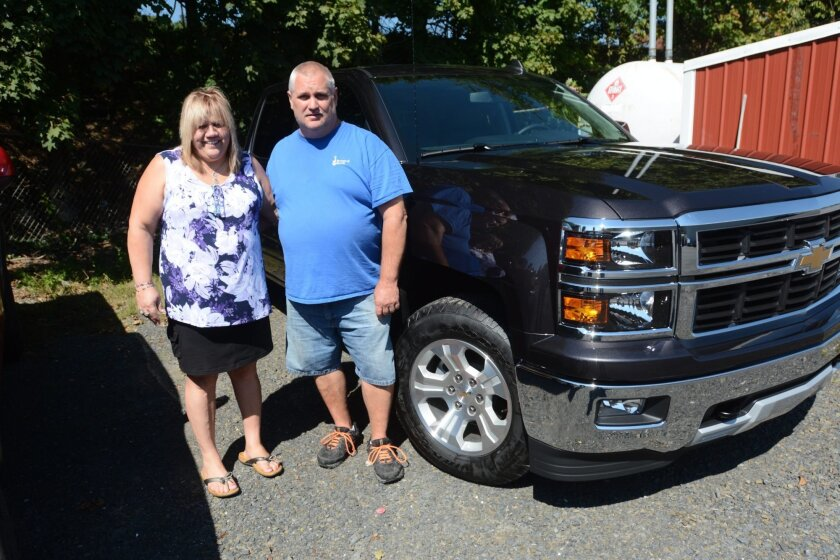 In this Sept. 17, 2015 photo, Joan Lechleitner and Kerry Titus, both of Pottsville, stand next to the 2015 Chevrolet Silverado 1500 Z71 the couple bought with money they won playing the Cash 5 lottery game in September 2015. The couple were charged Tuesday, May 31, 2016, along with two other former